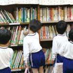 「絵本の部屋」の貸出風景。子どもたちがみずから読みたい本を選ぶ。貸し出し業務は保護者が運営する「絵本の会」のメンバーが交代で対応しているという