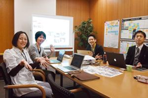 園児写真サービスを企画・開発中のプロジェクトチームのメンバー。右手奥がリーダーの徳間氏、時計回りに技術の今江氏と田口氏、デザインの塩飽氏