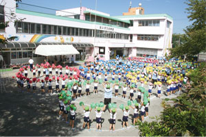 運動会の全体遊戯風景。えいすう幼稚園の園庭に、カラフルな円がきれいに描かれた