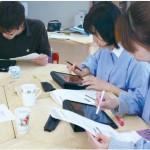 iPadを支給された先生たちが、園専用のコミュニティの試用をしている様子。画面をタッチして操作し、文字入力は表示されるキーボードから行う