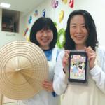 森井先生(左)と土屋園長(右)。園のシンボルであるくばがさ(久葉笠)と保護者との情報共有に大活躍のスライドショーを流すタブレットと一緒に。
