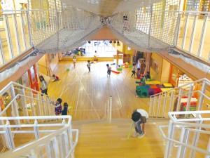 園舎の中心には大きな空間と特徴的なネット遊具。その両脇には、クラスルームが配置され、1階には乳児クラス、2階には幼児クラスが並んでいる