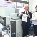 オルフィスGDと社員と一緒に、廣島清次代表取締役(左)。オプションを接続することで入園案内のステープル留めが自動化できるようになり、社員にも好評